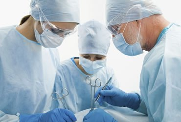 three chiropractic doctors wearing a blue scrub suits is performing a surgery