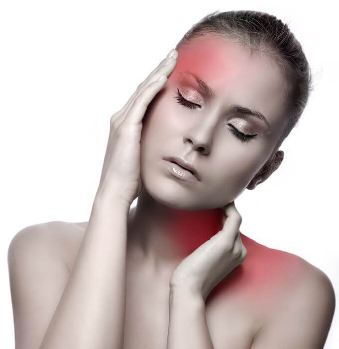 A woman holding her head and neck in pain